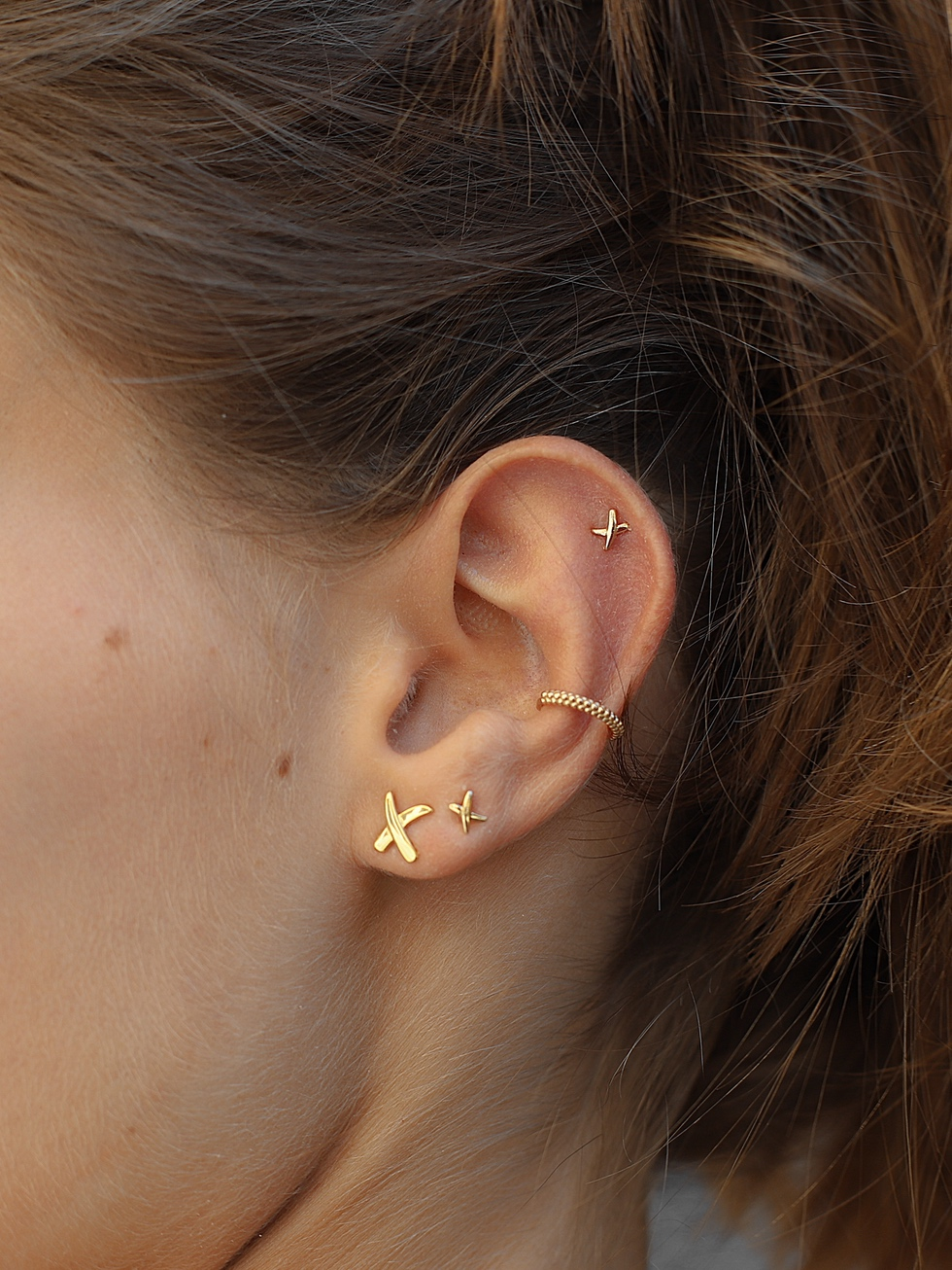 Tiny X gold earrings
